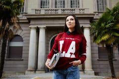 Estudiante que se coloca en el fondo de la entrada de la universidad que sostiene los libros Fotografía de archivo libre de regalías