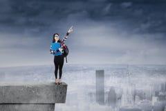 Estudiante que se coloca en tejado y que señala en el cielo Imagen de archivo