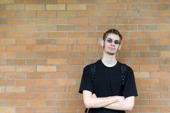 Estudiante que se inclina contra la pared de ladrillo Imagen de archivo