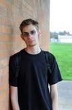 Estudiante que se inclina contra la pared de ladrillo Fotografía de archivo