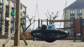 Estudiante que se relaja en el oscilación en patio, la libertad y la inspiración de la ciudad metrajes