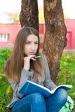 Estudiante que se sienta bajo árbol y pensamiento Imágenes de archivo libres de regalías