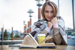 Estudiante que se sienta con el libro y el café en café Imagen de archivo