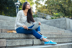 Estudiante que se sienta con el ordenador portátil al aire libre Imagenes de archivo