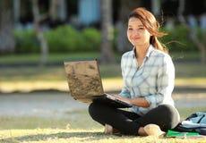 Estudiante que se sienta con la computadora portátil Imagen de archivo