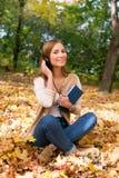 Estudiante que se sienta con los auriculares entre las hojas de arce Fotos de archivo libres de regalías