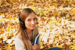 Estudiante que se sienta con los auriculares entre las hojas de arce y que mira u Imágenes de archivo libres de regalías