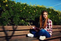 Estudiante que se sienta en banco de madera en el campus Fotografía de archivo