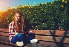 Estudiante que se sienta en banco de madera en el campus Imagenes de archivo