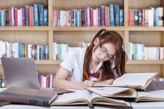 Estudiante que se sienta en biblioteca mientras que escribe en el libro Fotografía de archivo