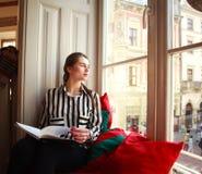 Estudiante que se sienta en casa por la ventana con el libro Fotografía de archivo libre de regalías