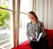 Estudiante que se sienta en casa por la ventana con el libro Imágenes de archivo libres de regalías