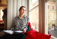 Estudiante que se sienta en casa por la ventana con el libro Imagen de archivo libre de regalías