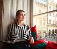 Estudiante que se sienta en casa por la ventana con el libro Imagenes de archivo