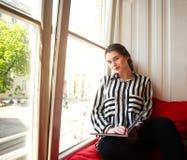 Estudiante que se sienta en casa por la ventana con el libro Foto de archivo libre de regalías