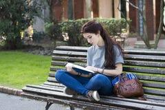 Estudiante que se sienta en el banco de madera y el libro azul leído, al aire libre Imagenes de archivo