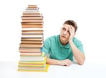 Estudiante que se sienta en el escritorio con la alta pila de libros Imagen de archivo libre de regalías