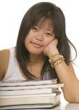 Estudiante que se sienta en el escritorio con sus libros de escuela fotos de archivo