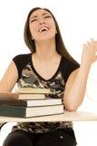 Estudiante que se sienta en el escritorio por completo de la risa de los libros Imagen de archivo libre de regalías