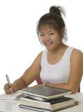Estudiante que se sienta en el escritorio y que hace la preparación Foto de archivo libre de regalías