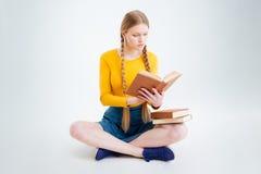 Estudiante que se sienta en el libro del piso y de lectura Imagen de archivo