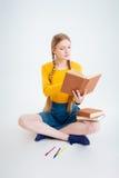 Estudiante que se sienta en el libro del piso y de lectura Foto de archivo