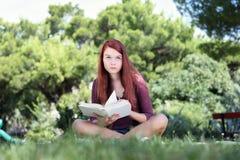 Estudiante que se sienta en el parque con un libro que mira para arriba Imagen de archivo libre de regalías