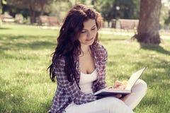 Estudiante que se sienta en el parque en la hierba y que lee un libro Fotografía de archivo