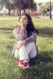 Estudiante que se sienta en el parque en la hierba y que mira para arriba soñador Imagenes de archivo