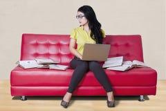 Estudiante que se sienta en el sofá mientras que hace la preparación Imágenes de archivo libres de regalías