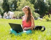 Estudiante que se sienta en hierba con el ordenador portátil Mujer joven hermosa con el cuaderno en línea en el parque outdoor Dí Fotografía de archivo libre de regalías