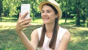 Estudiante que se sienta en hierba en el campus de la universidad que tiene charla video vía el app en línea en el teléfono móvil almacen de video