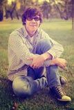 Estudiante que se sienta en la hierba al aire libre Foto de archivo
