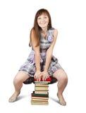 Estudiante que se sienta en la pila de libros Foto de archivo
