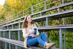 Estudiante que se sienta en tribuna del deporte con el libro y que sonríe en la cámara Fotografía de archivo
