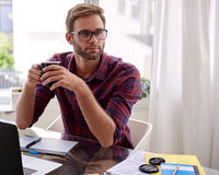 Estudiante que se sienta en un escritorio con café en sus manos Imagen de archivo