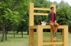 Estudiante que se sienta en una silla grande Imágenes de archivo libres de regalías
