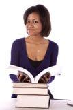 Estudiante que sonríe con la pila de libros Imagen de archivo libre de regalías