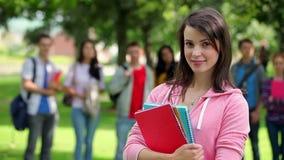 Estudiante que sonríe en la cámara con los amigos que se colocan detrás de ella en hierba metrajes
