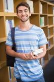 Estudiante que sonríe en la cámara en biblioteca foto de archivo libre de regalías