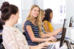 Estudiante que sonríe en la cámara en clase del ordenador Foto de archivo libre de regalías