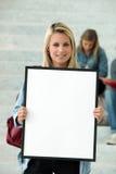 Estudiante que sostiene el cartel en blanco Fotos de archivo
