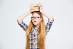 Estudiante que sostiene los libros en la cabeza Foto de archivo libre de regalías