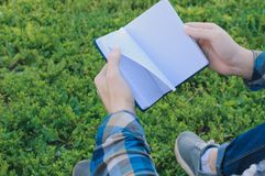 Estudiante que sostiene un libro que se sienta afuera Fotos de archivo libres de regalías