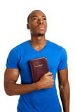 Estudiante que sostiene una biblia que mira para arriba Foto de archivo libre de regalías