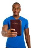 Estudiante que sostiene una biblia que muestra la consolidación Foto de archivo