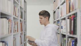 Estudiante que toma los libros del estante en biblioteca almacen de video