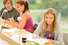 Estudiante que toma notas en sitio de estudio Fotos de archivo