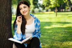 Estudiante que toma notas en su cuaderno Sentada de la mujer joven Fotografía de archivo libre de regalías