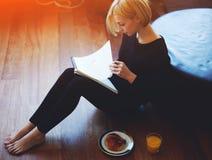 Estudiante que toma notas en su cuaderno sobre el desayuno Imagen de archivo